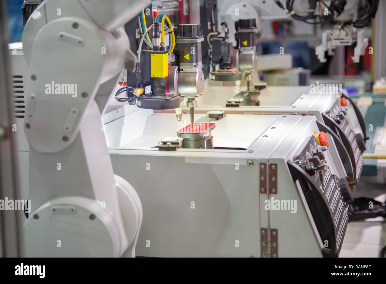 Robotic arm loading and unloading mobile phone case to engrave in CNC laser machine - Stock Image