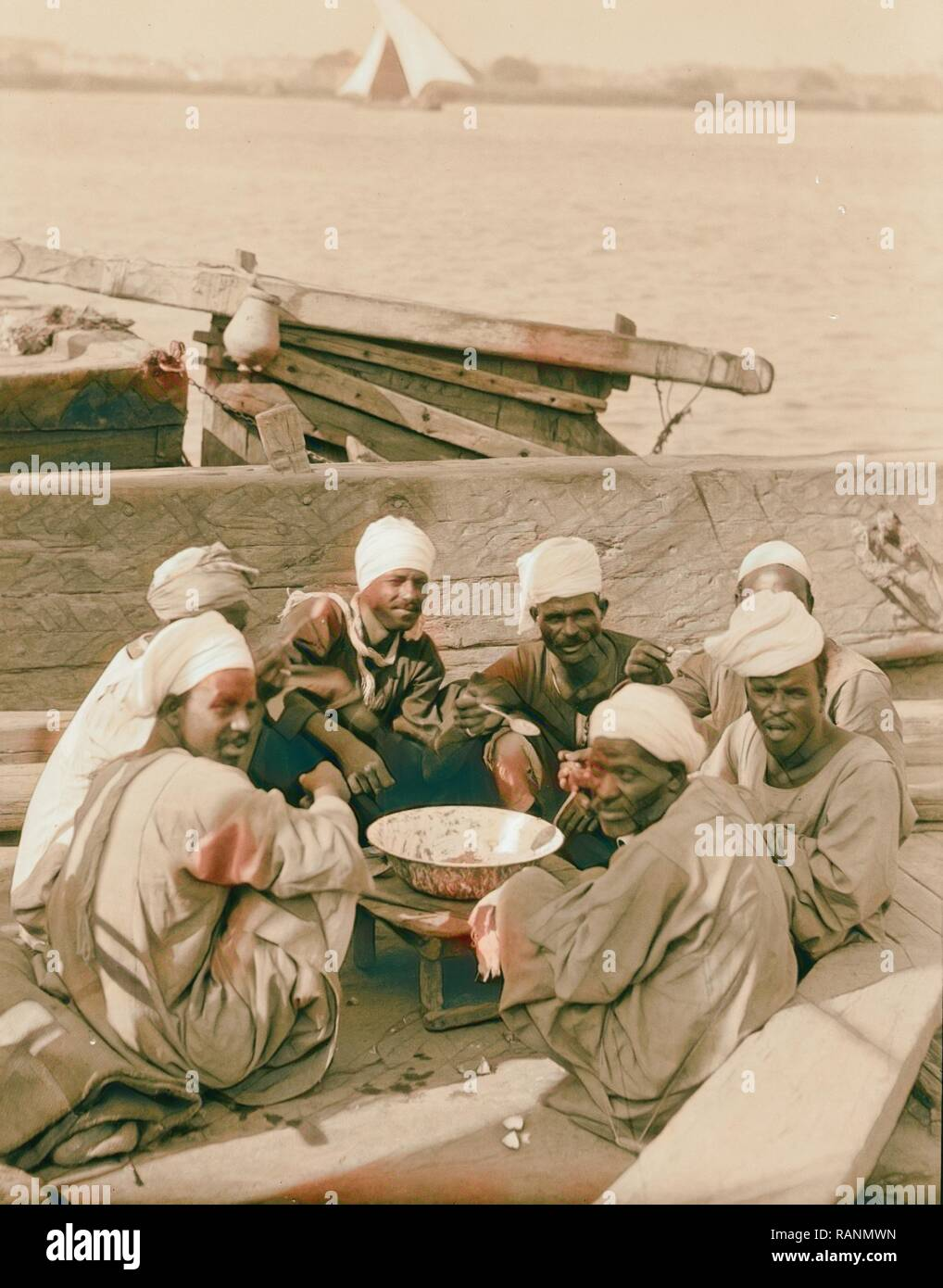 Cairo and district, Egypt. Luncheon on the Nile. Boatmen at their noon-day meal. 1934, Egypt, Cairo. Reimagined - Stock Image
