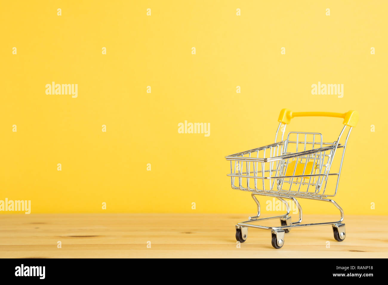 Shopping cart on wooden table with yellow background - Stock Image