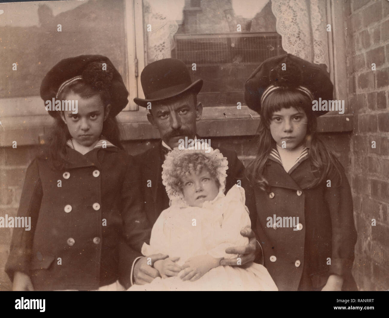 Vintage Victorian / Edwardian Photograph of a Father and His Three Daughters. The Youngest Child May Be Deceased Due To The Facial Expression. - Stock Image
