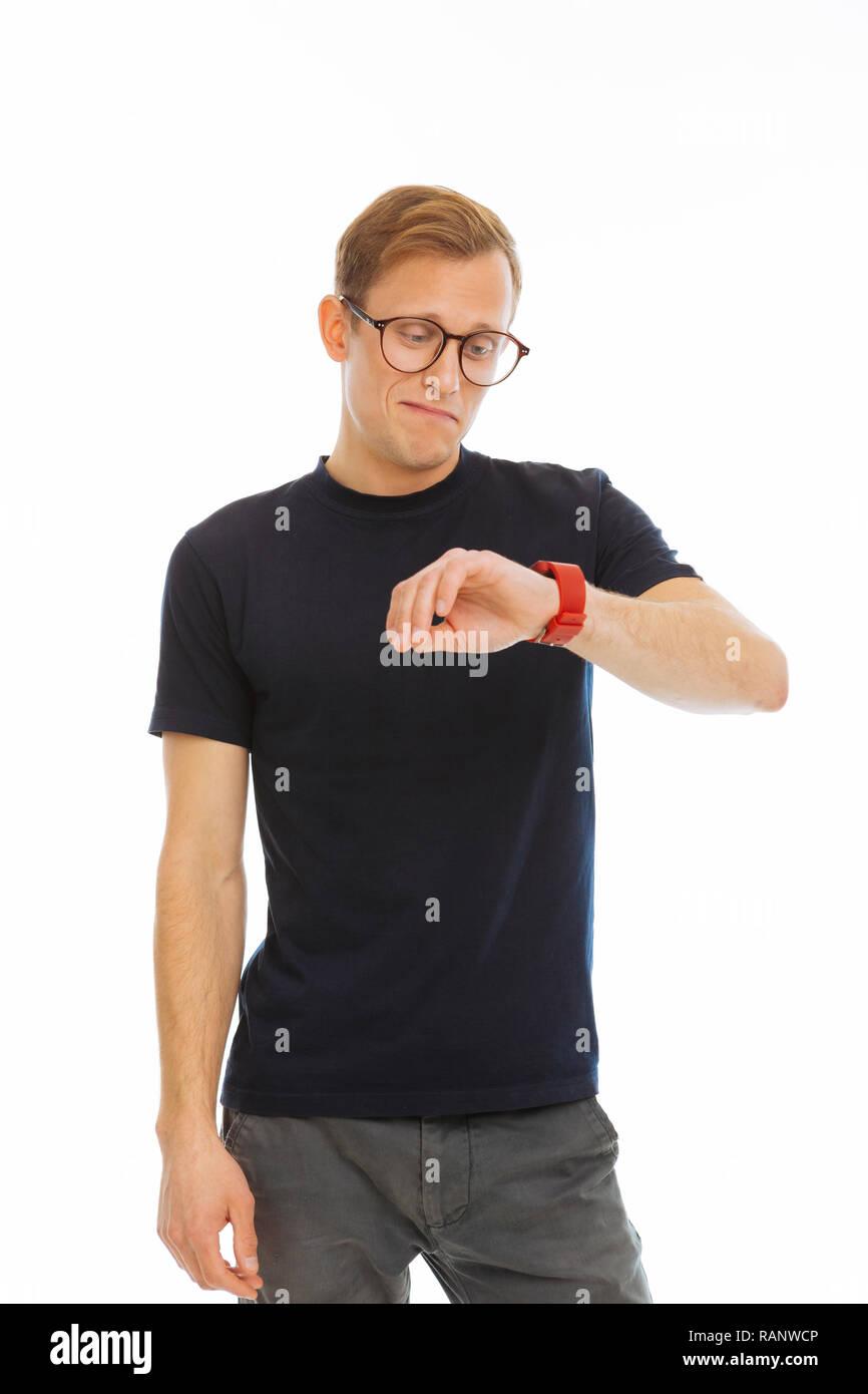 Joyful smart man looking at his smartwatch - Stock Image