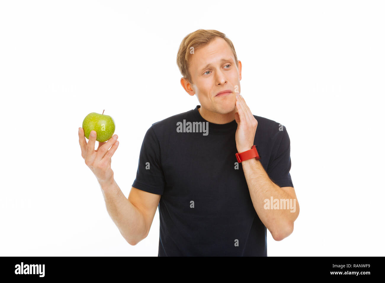Unhappy cheerless young man having a toothache - Stock Image
