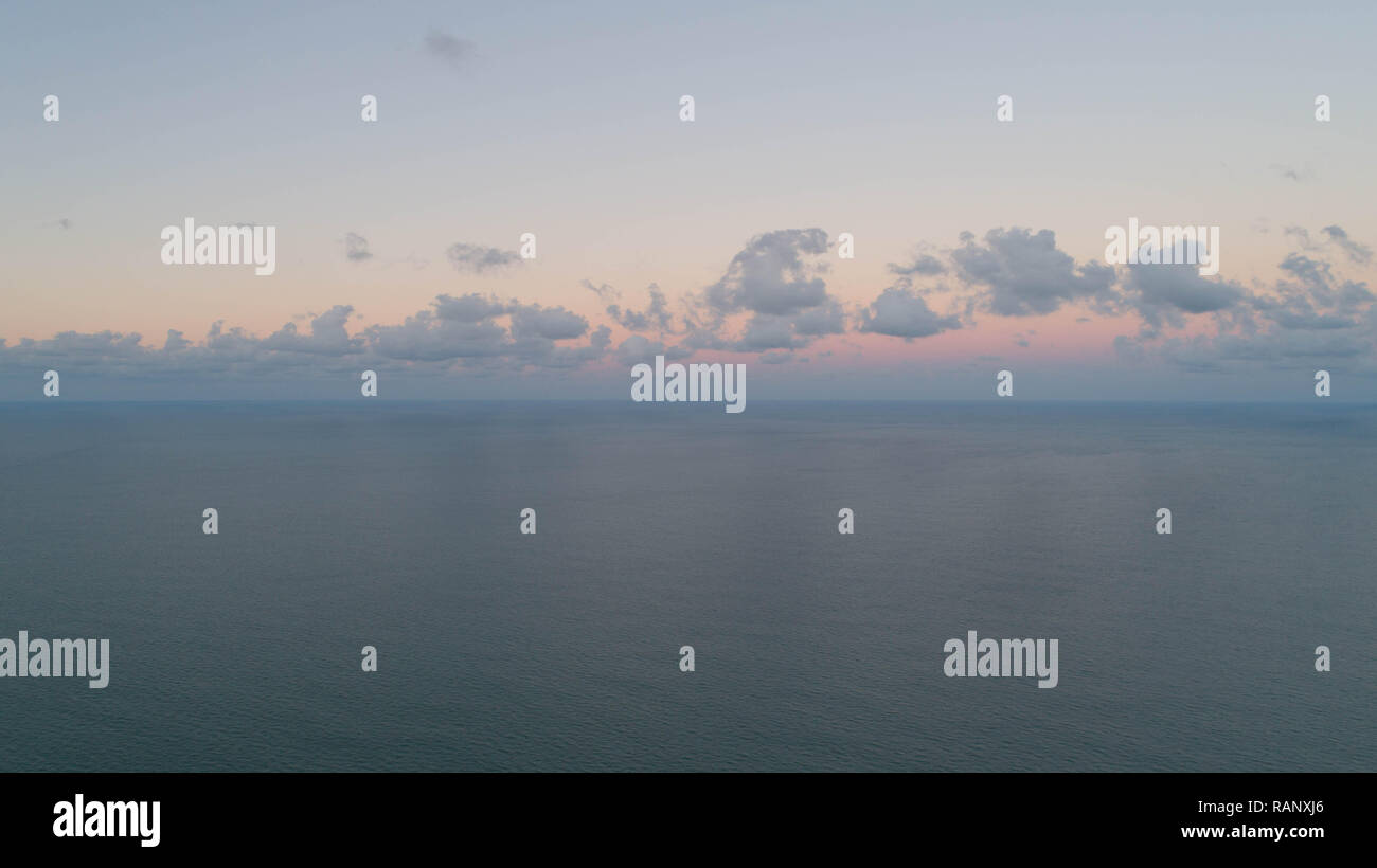 Drone Picture Aerial Image Tranquil Early Morning Day View Ocean Cloudy Horizon At Daybreak With Beautiful Colors of Dawn Sun Trying to Break Clouds. - Stock Image