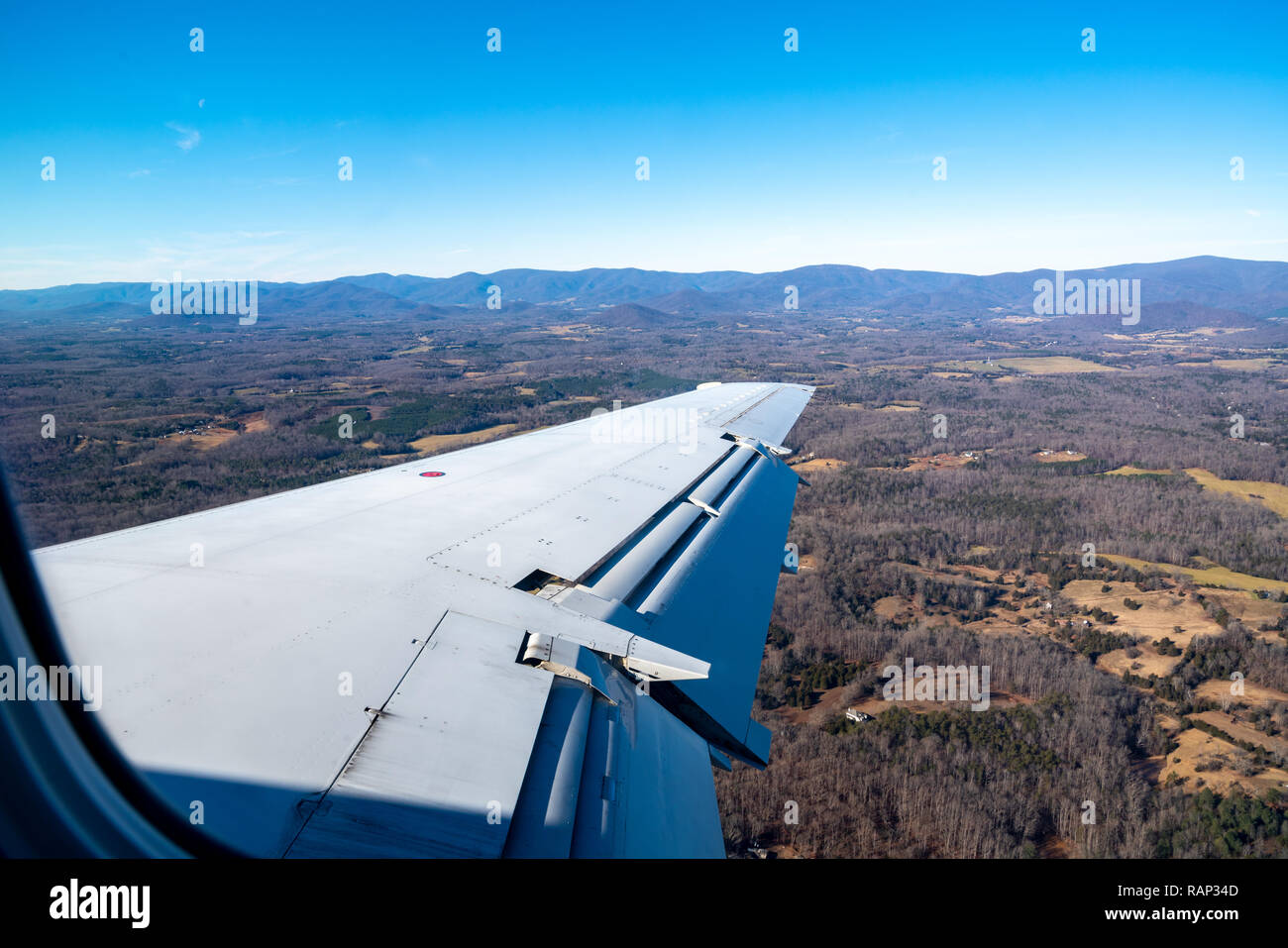 New York, USA,  29DEC2018 - The wing of an Embraer ERJ-135 twin-jet is seen against the landscape as it descends towards Charlottesville, Virginia.  P - Stock Image