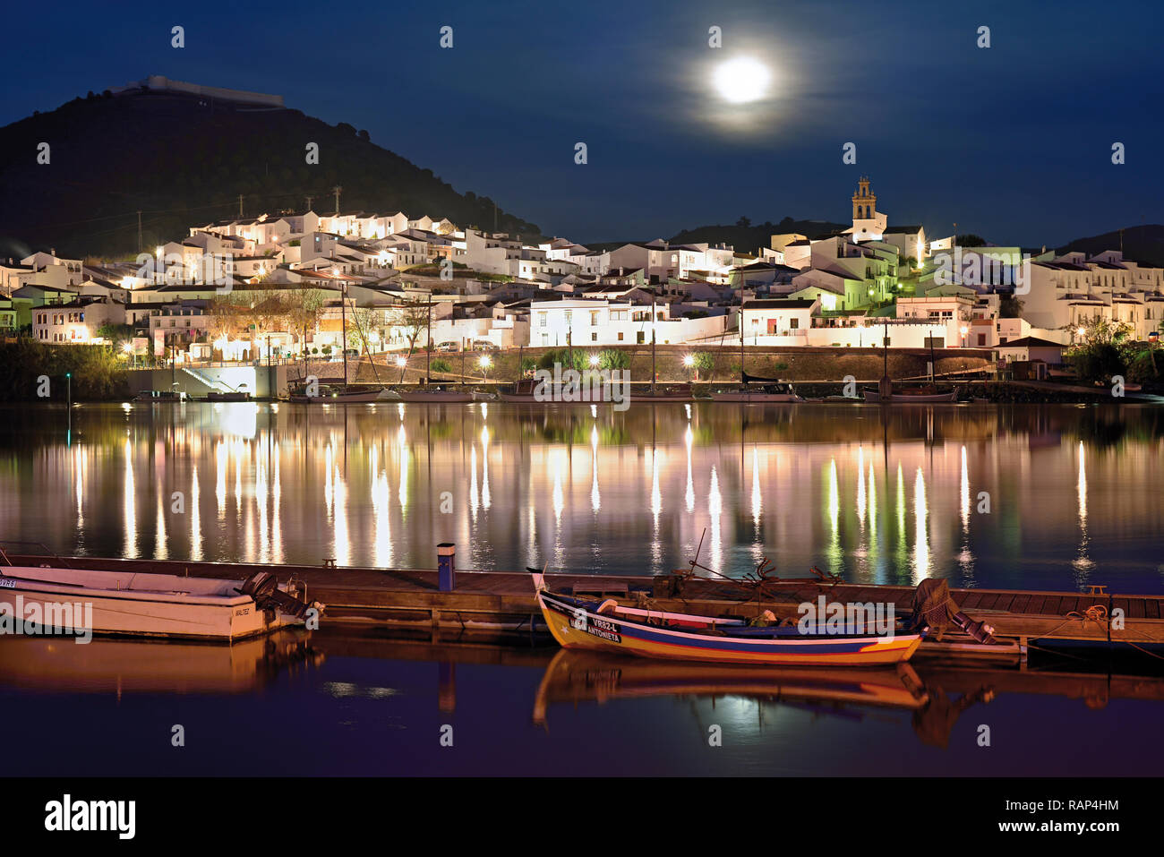 Romantic white washed riverside village with moonlight and wooden fishing boats anchoring at quay (view from Portugal to Spain) - Stock Image