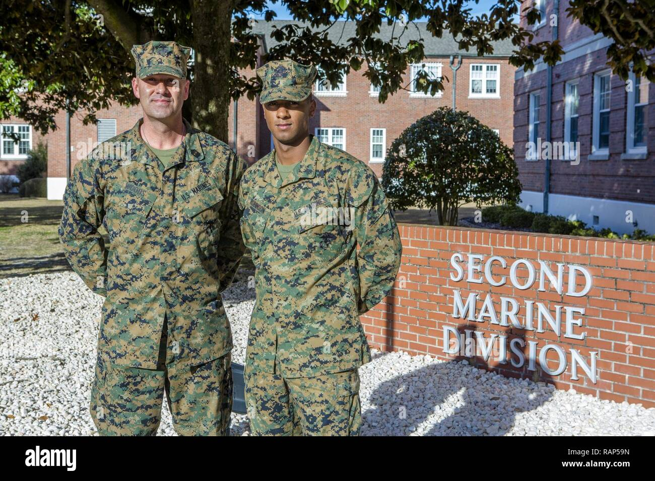 U.S. Marine Corps Sgt. Maj. Michael P. Woods, sergeant major, 2nd Marine Division (2d MARDIV), stands with Cpl. Demarcus R. Robinson, 2d MARDIV, following a morning colors ceremony on Camp Lejeune, N.C., Feb. 22, 2017. During this ceremony Maj. Gen. John K. Love, commanding general, 2d MARDIV, recognized Marines and Sailors, within the 2d MARDIV, who set themselves apart from their peers during the previous quarter by demonstrating their leadership abilities, espirit de corps and their skill and will. Stock Photo