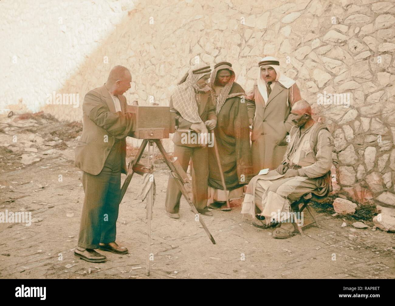 Peasants being photographed for identity cards, headdress removed. Photographer with camera taking a photograph of a reimagined - Stock Image