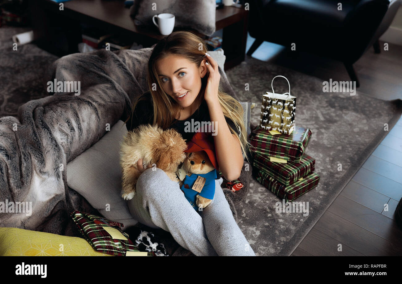 Attractive blonde girl celebrating winter holidays at home with her small doggy, playing and pet him. Rest on grey comfortable couch with pillows. - Stock Image