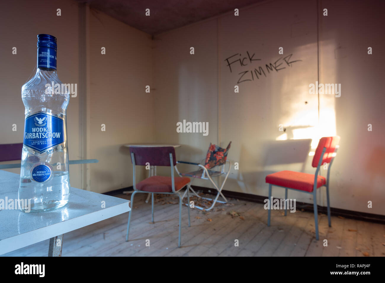 Prerow, Germany - December 30, 2018: View of a bottle of vodka and red chairs in a barrack of the former training camp of the Gesellschaft für Sport u - Stock Image