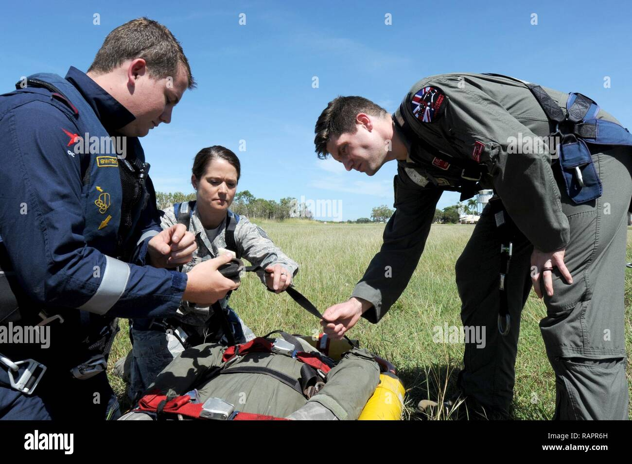 Rescue Crewman Kurt Pride, Royal Australian Air Force Base Tindal helicopter unit member, U.S. Air Force Capt. Paul Ward, 90th Fighter Squadron Flight Doctor, and Tech. Sgt. Layla Dispense, 90th FS Independent Duty Medical Technician, prepare a dummy for transport on a stretcher during helicopter rescue training at RAAF Base Tindal, Feb. 28, 2017. Ward and Dispense are deployed to Australia as part of the Enhanced Air Cooperation, a joint training and exercise initiative under the Force Posture Agreement between the U.S. and Australian governments. - Stock Image