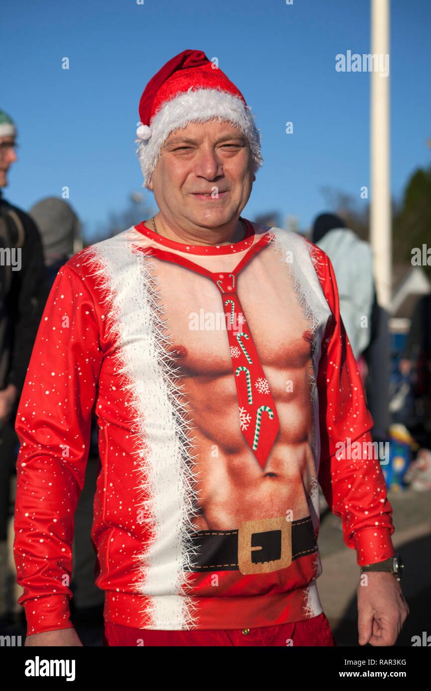 Man in fancy dress at the New Year's Day swim at Rhu Marina, Argyll, Scotland. - Stock Image