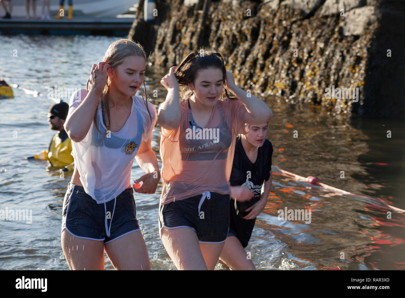 Two girls emerging from the water at the annual New Year's Day swim at Rhu Marina, Scotland - Stock Image