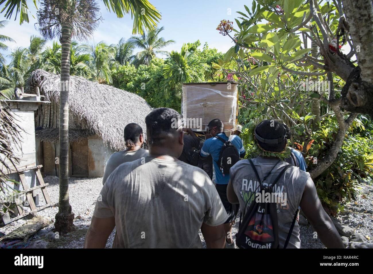 Islanders carry a box of humanitarian supplies through their village