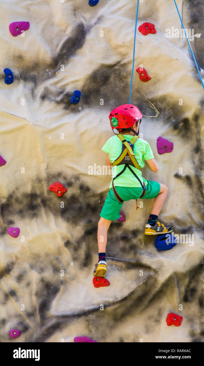 shot of little boy in a harness climbing a wall with grips. - Stock Image