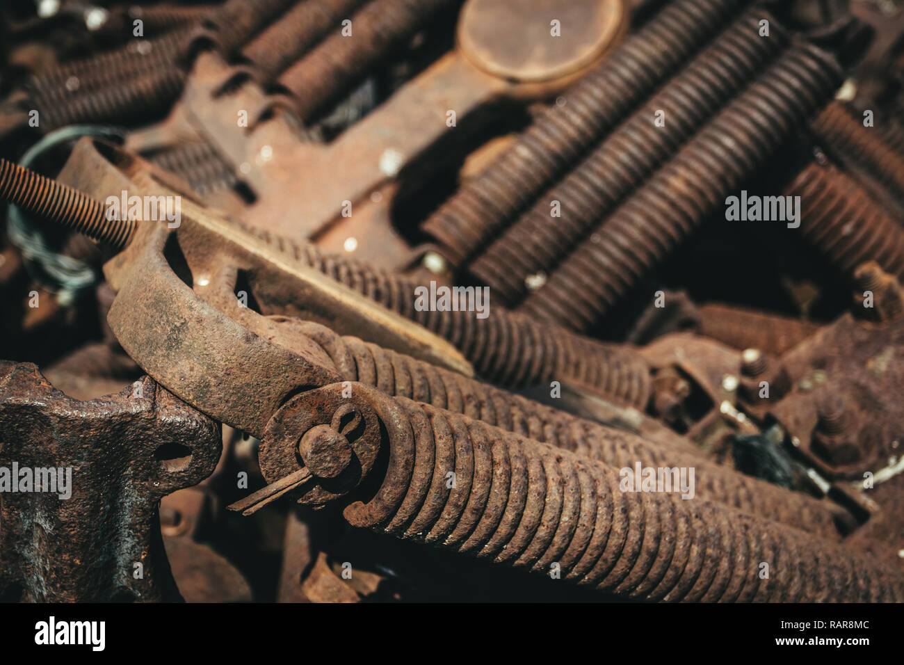 Rusty railroad car spring assemblies laying in a pile on the ground. - Stock Image