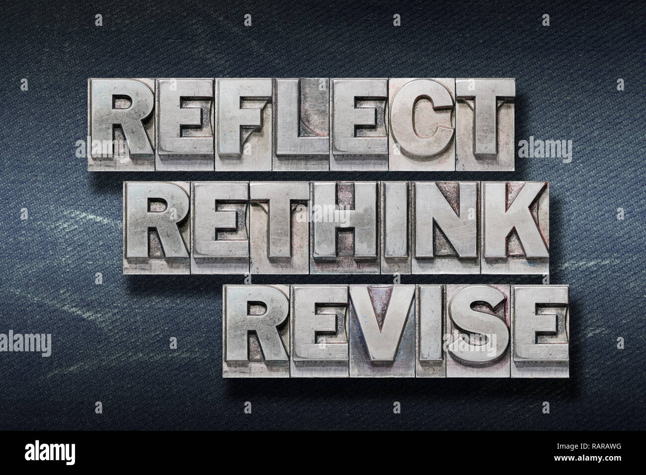 reflect rethink revise words made from metallic letterpress on dark jeans background - Stock Image