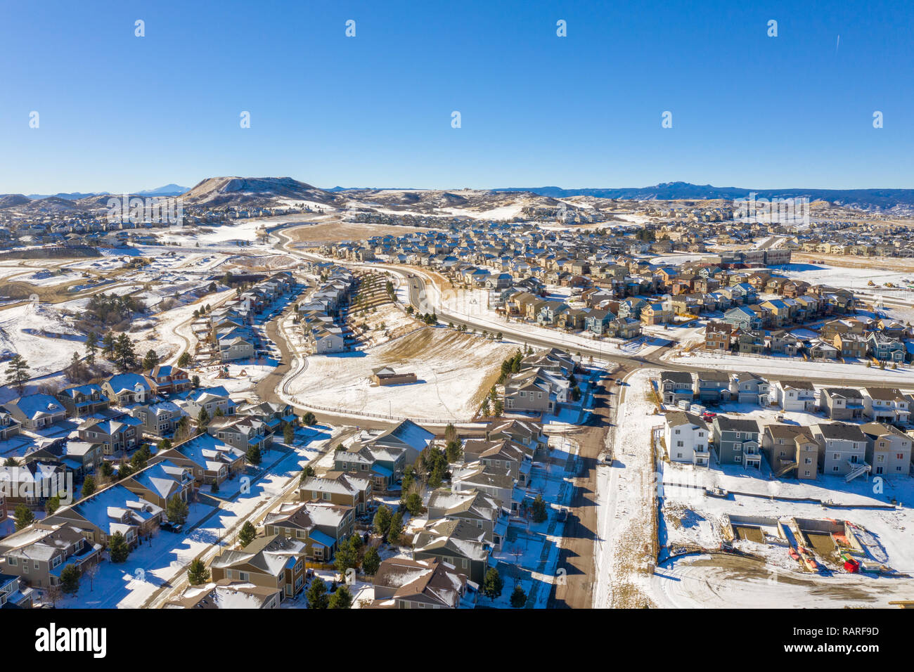 A great photo illustrating Denver urban sprawl and the Colorado housing boom as it continues even in the winter snow - Stock Image