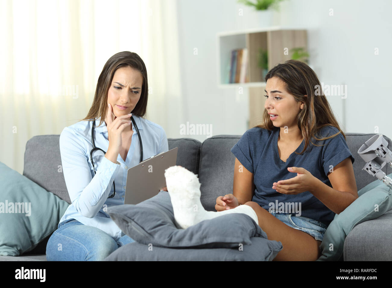 Worried doctor and patient talking sitting on a couch in the living room at home - Stock Image