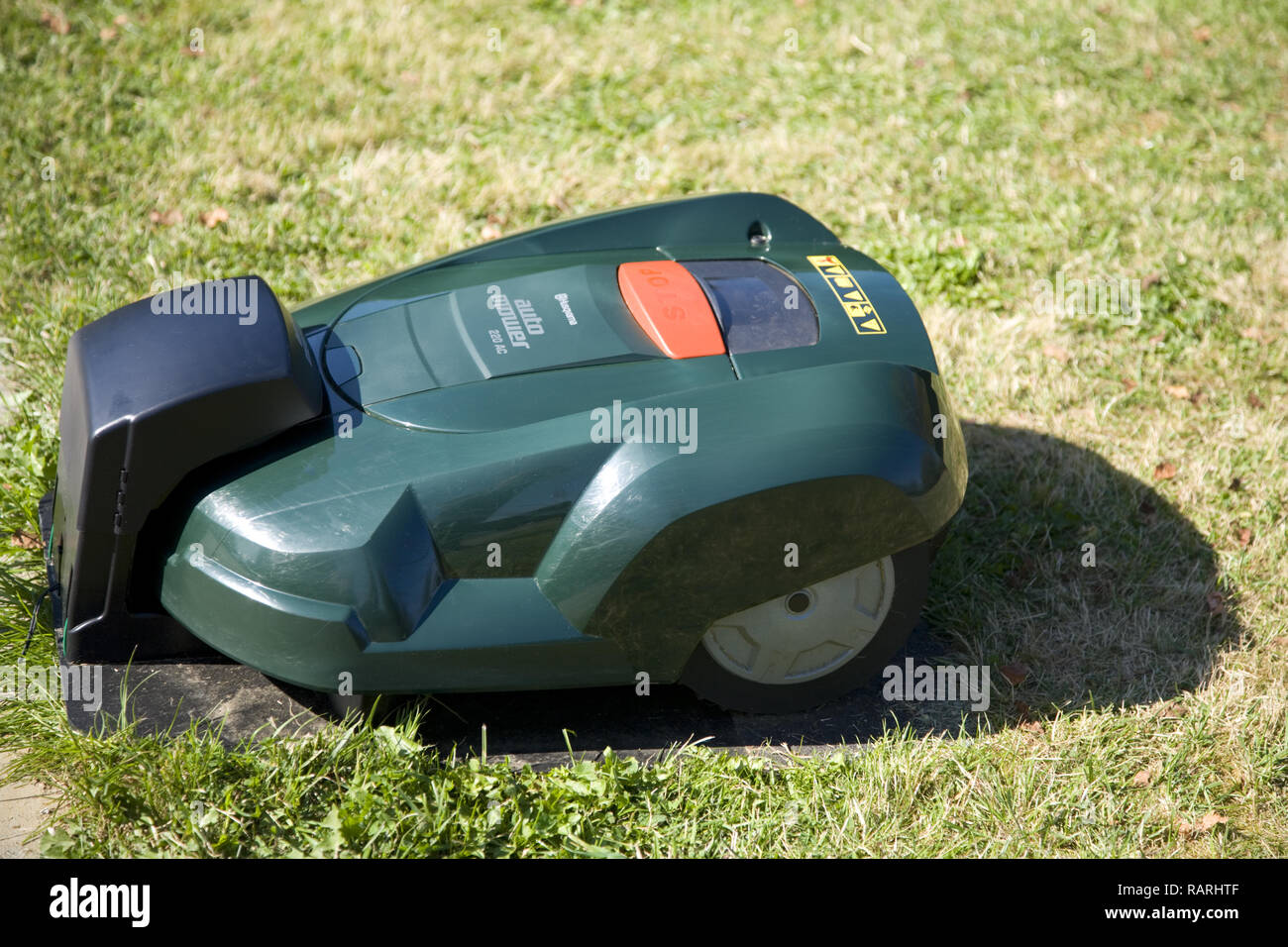 Green automatic robot lawnmower docked in its charging station, top view - Stock Image