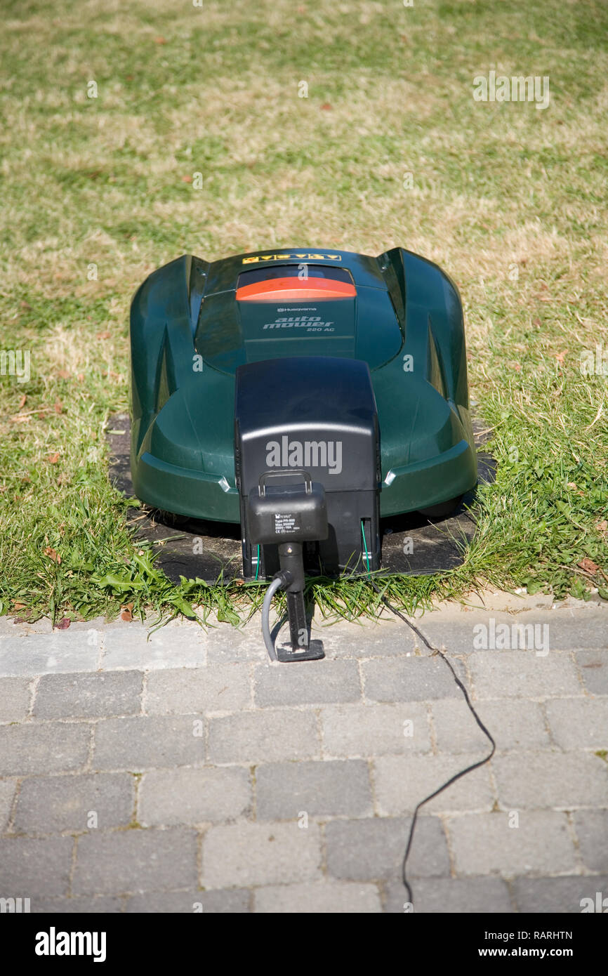 Green automatic robot lawnmower docked in its charging station near a patio, face on front view - Stock Image