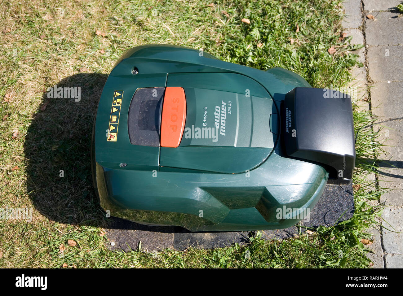 Green automatic robot lawnmower docked in its charging station near a patio, top view Stock Photo