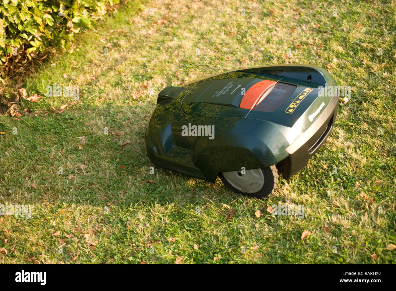 Automatic robot lawn mower cutting grass and heading towards a hedge - Stock Image
