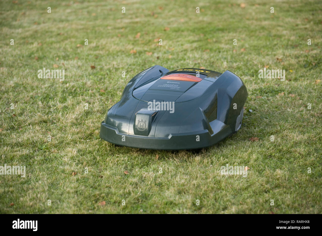 Automatic robot lawn mower cutting grass and seen from th top front - Stock Image