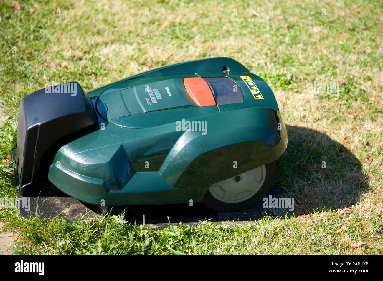 Green automatic robot lawnmower docked in its charging station near a patio - Stock Image
