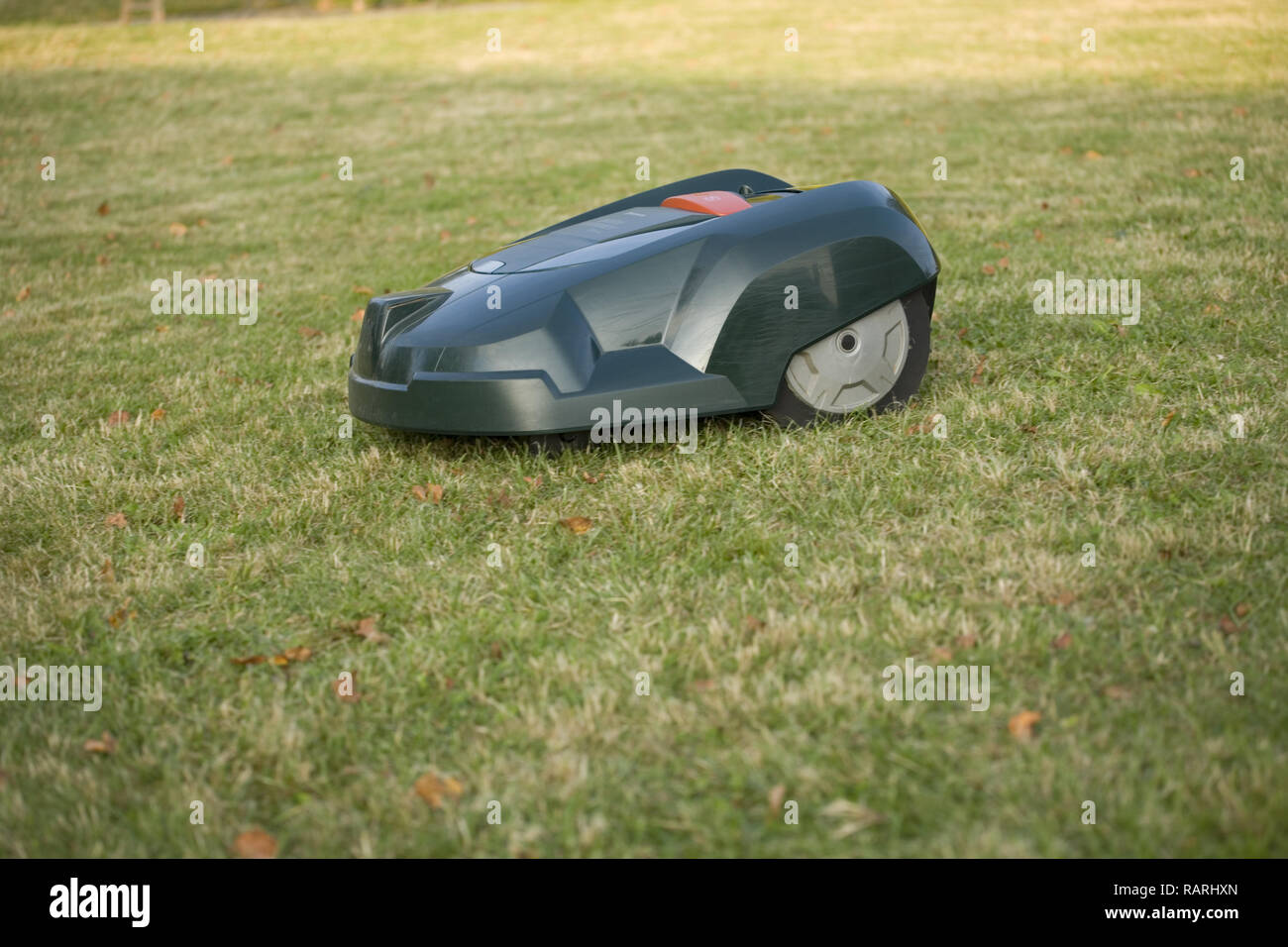 Automatic robot lawn mower cutting grass side view Stock Photo