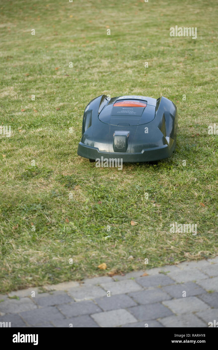 Automatic robot lawn mower cutting grass heading towards a patio - Stock Image