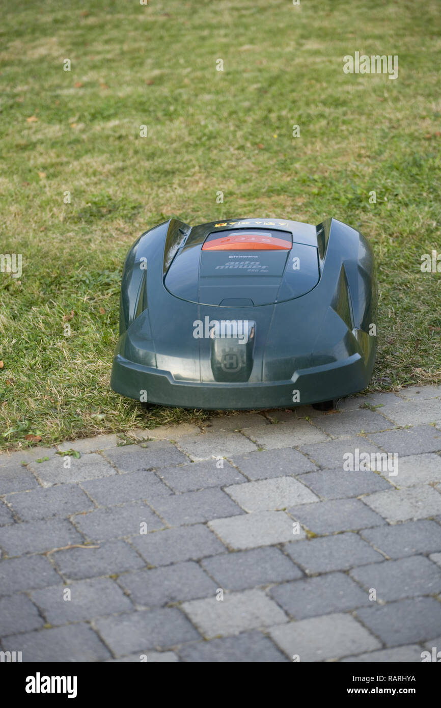 Automatic robot lawn mower cutting grass next to patio - Stock Image