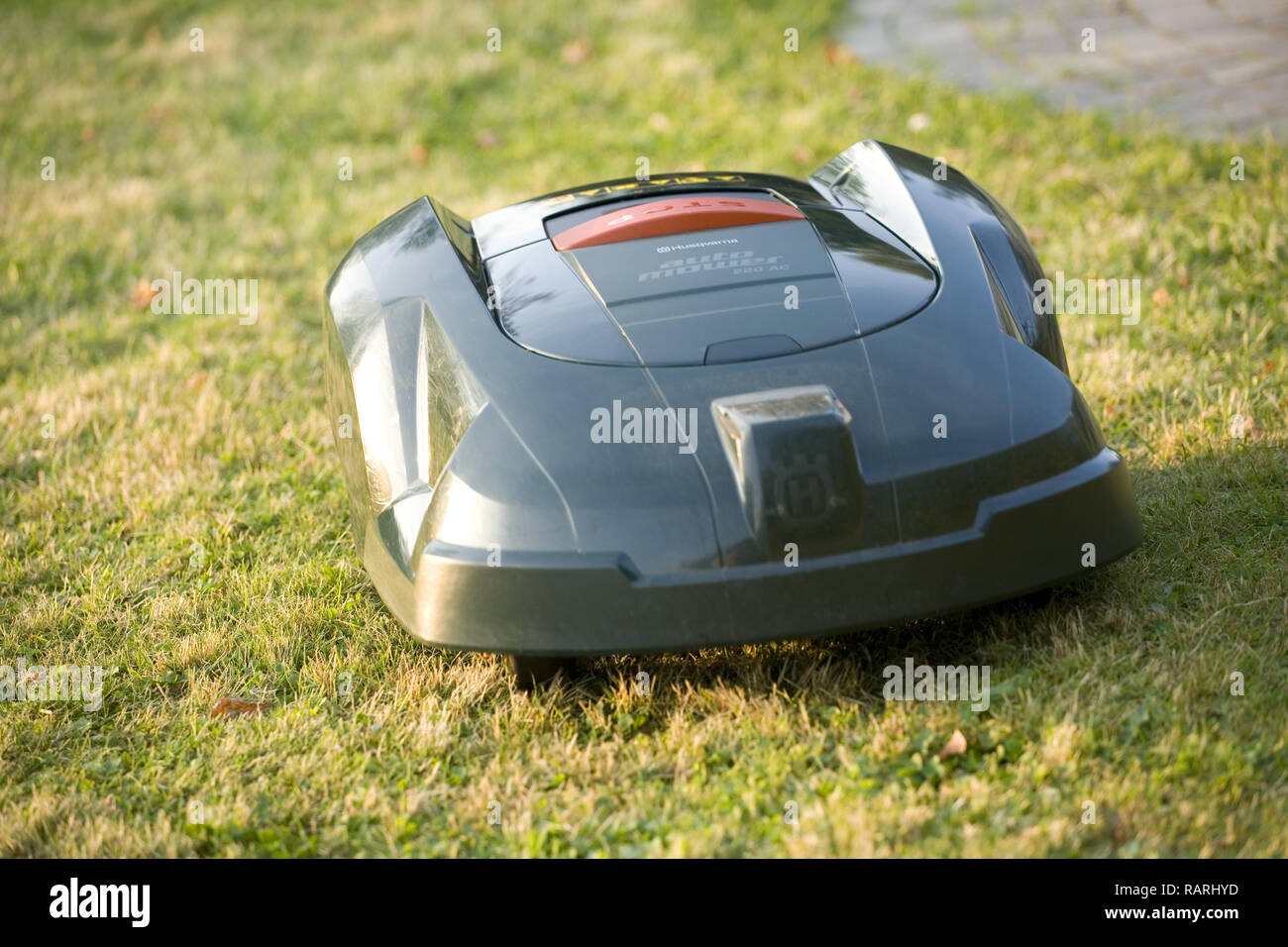 Automatic robot lawn mower cutting grass close up heading to camera - Stock Image
