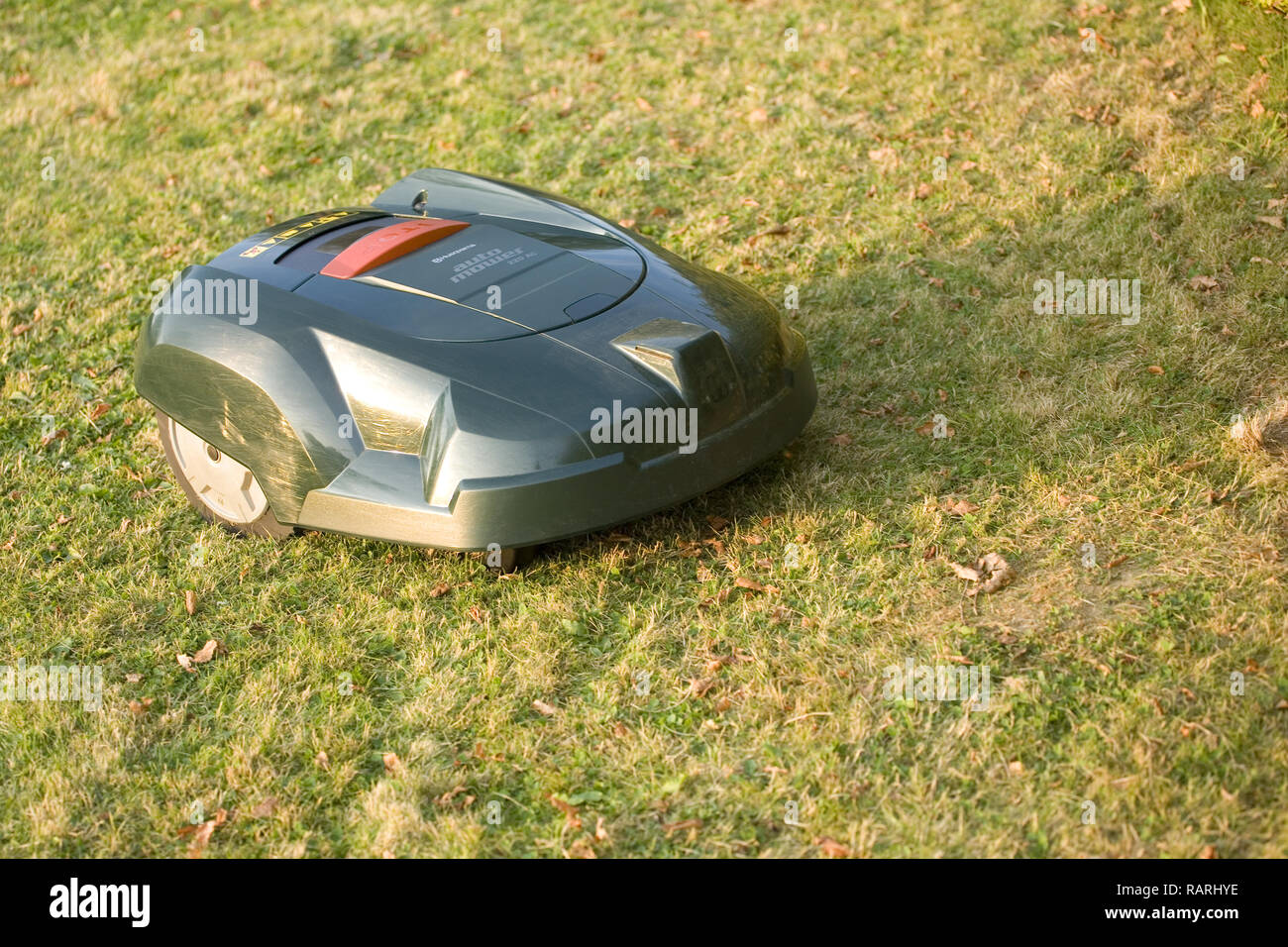 Automatic robot lawn mower cutting grass from a side position view - Stock Image
