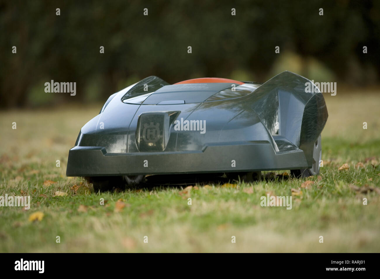 Automatic robot lawn mower cutting grass heading towards camera close up Stock Photo