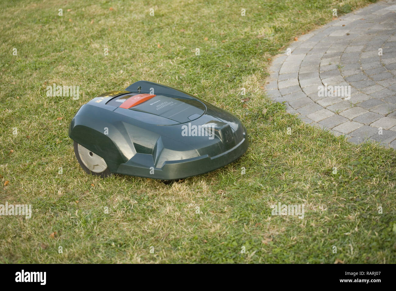 Automatic robot lawn mower cutting grass near a patio - Stock Image
