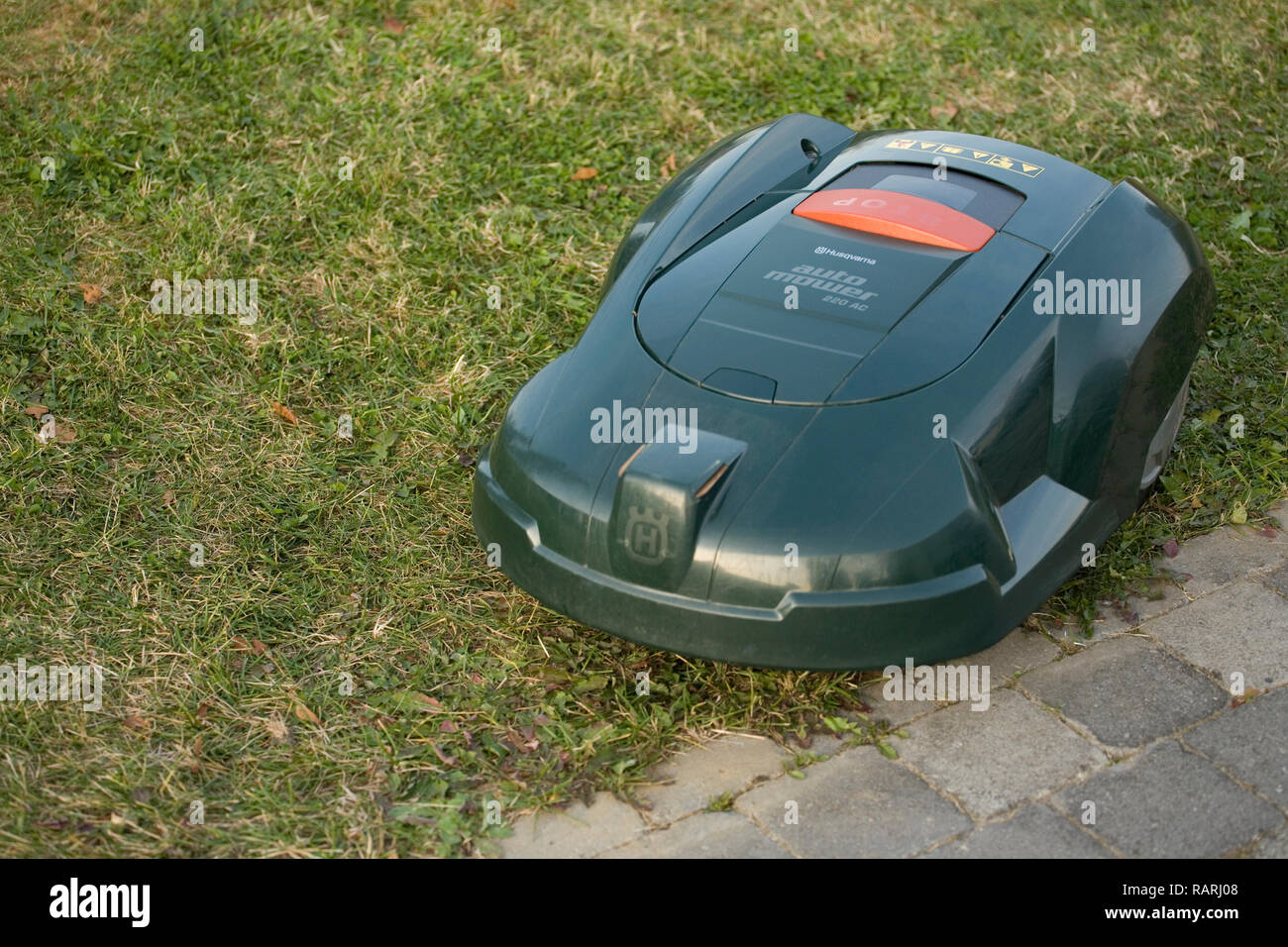 Top view of a green automatic robot lawn mower cutting grass - Stock Image