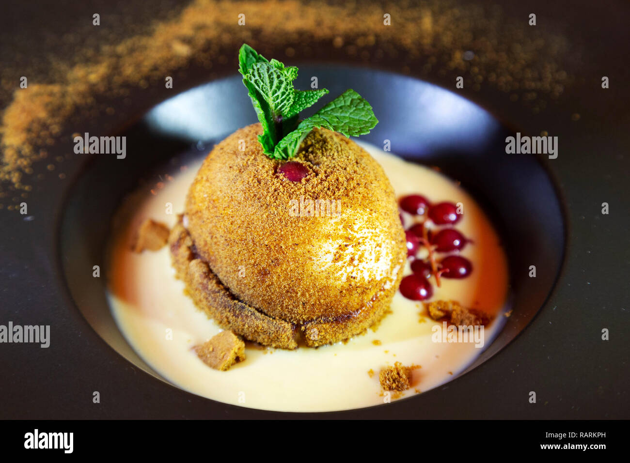 A seasonal pudding, served at Christmastime in Arras, France. The dessert is creatively dressed to look like a pudding and features Spectaculus. - Stock Image