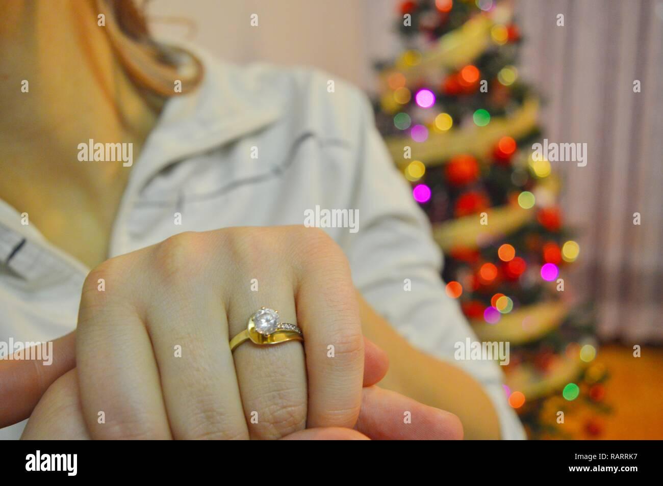 Wedding ring on a girl's hand. Proposal around Christmas. - Stock Image