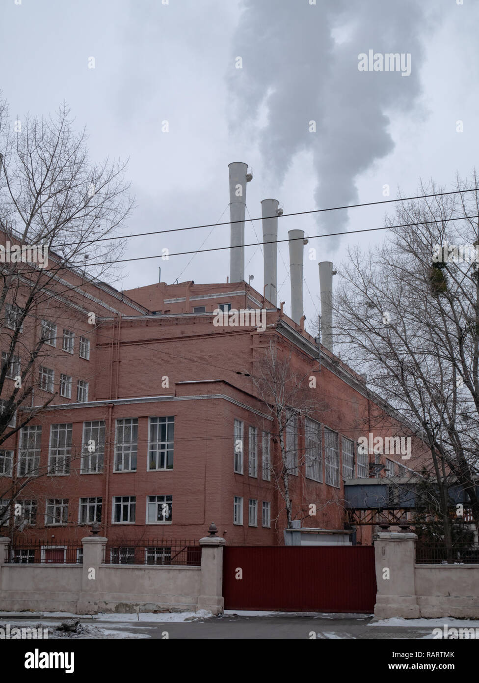 factory plant building with long chimneys producing some light industry goods - Stock Image