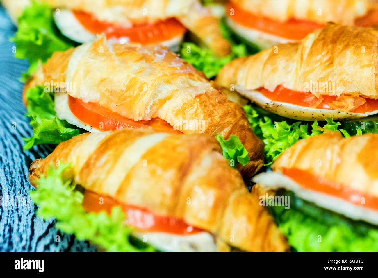 Close up fresh croissants with salad, ham and cheese on table - Stock Image