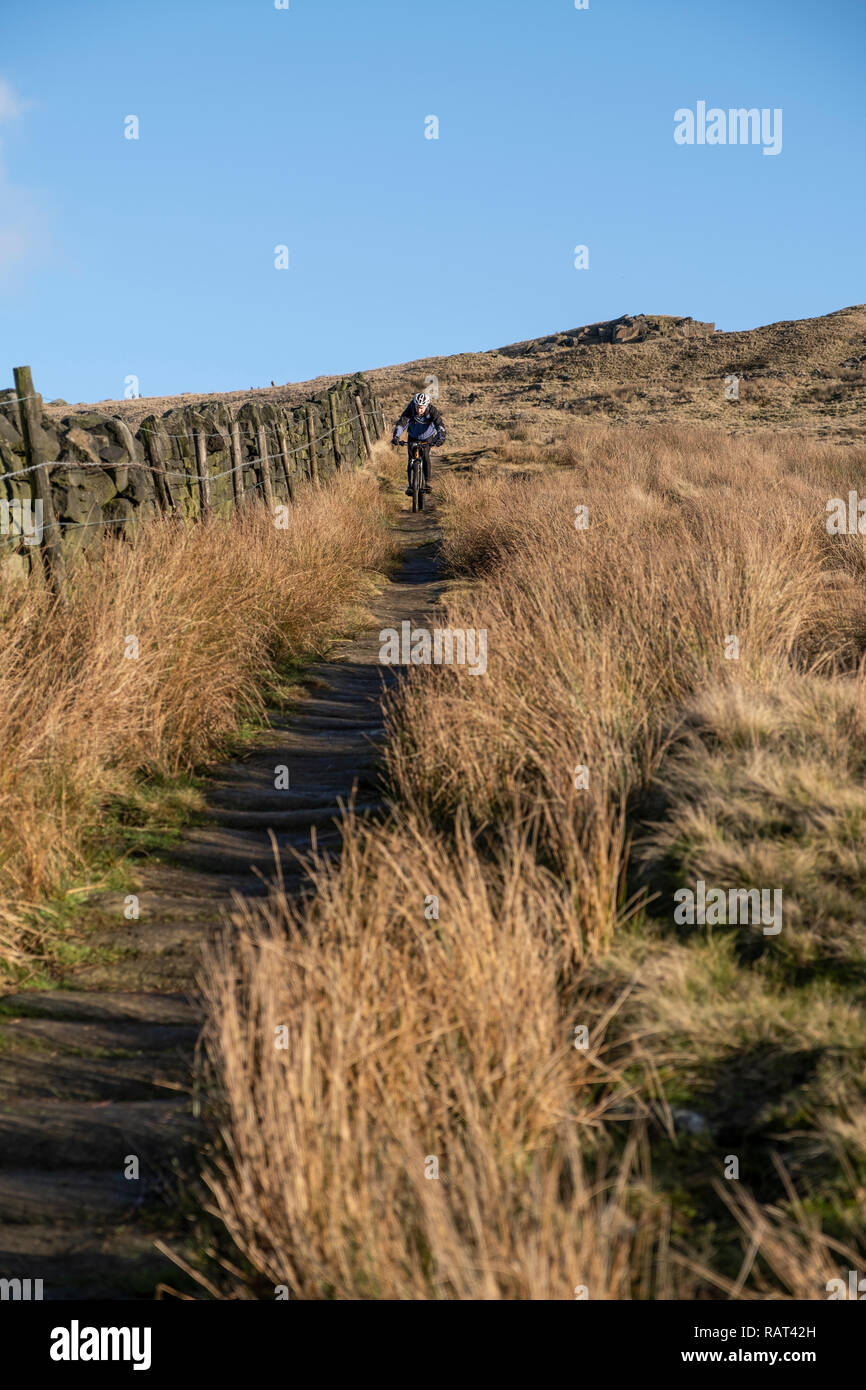 A Mountain bike rider on a Pack horse trail above the Village of  Lumbutts, Calderdale, West Yorkshire, England. Stock Photo