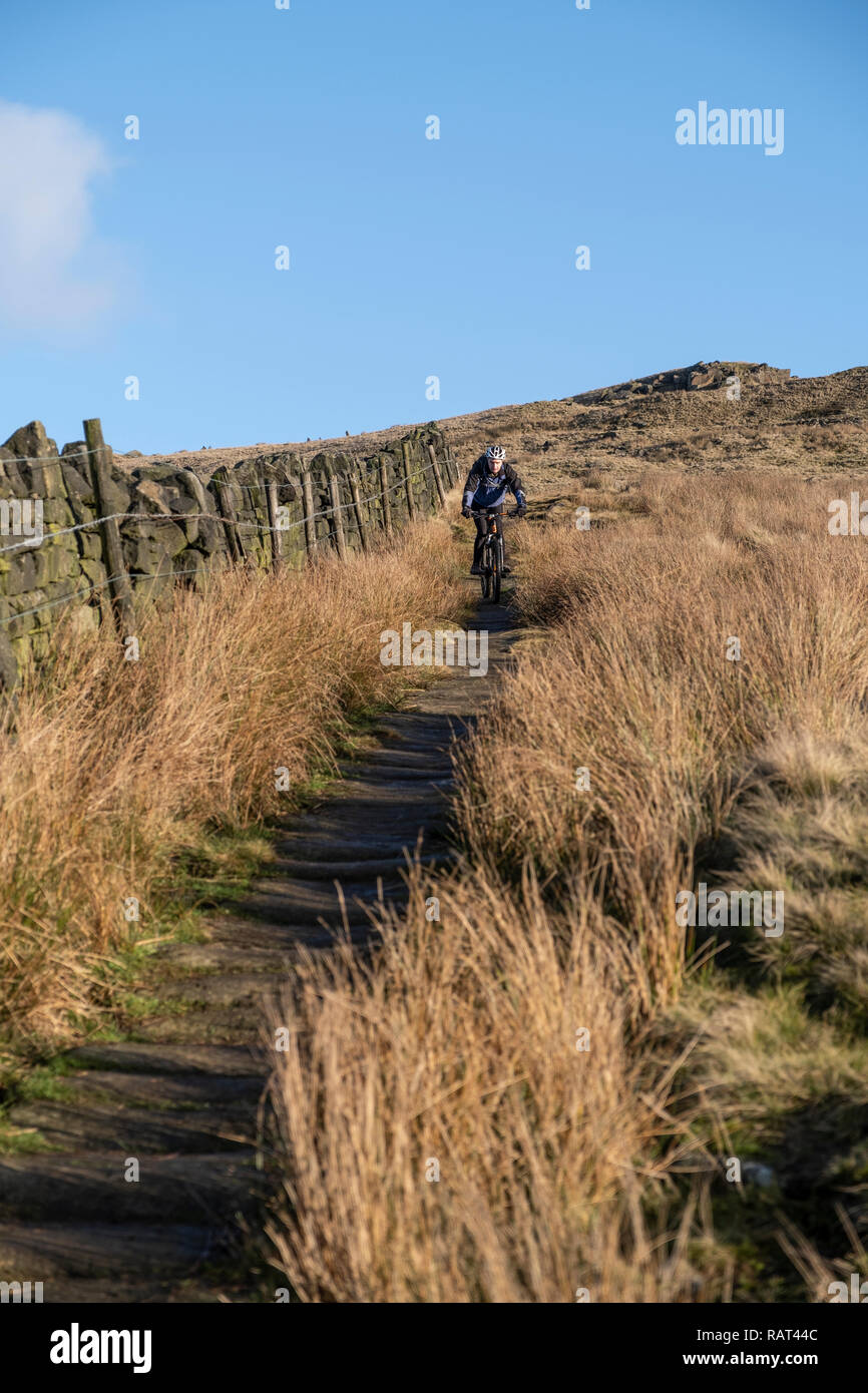 A Mountain bike rider on a Pack horse trail above the Village of  Lumbutts, Calderdale, West Yorkshire, England. - Stock Image
