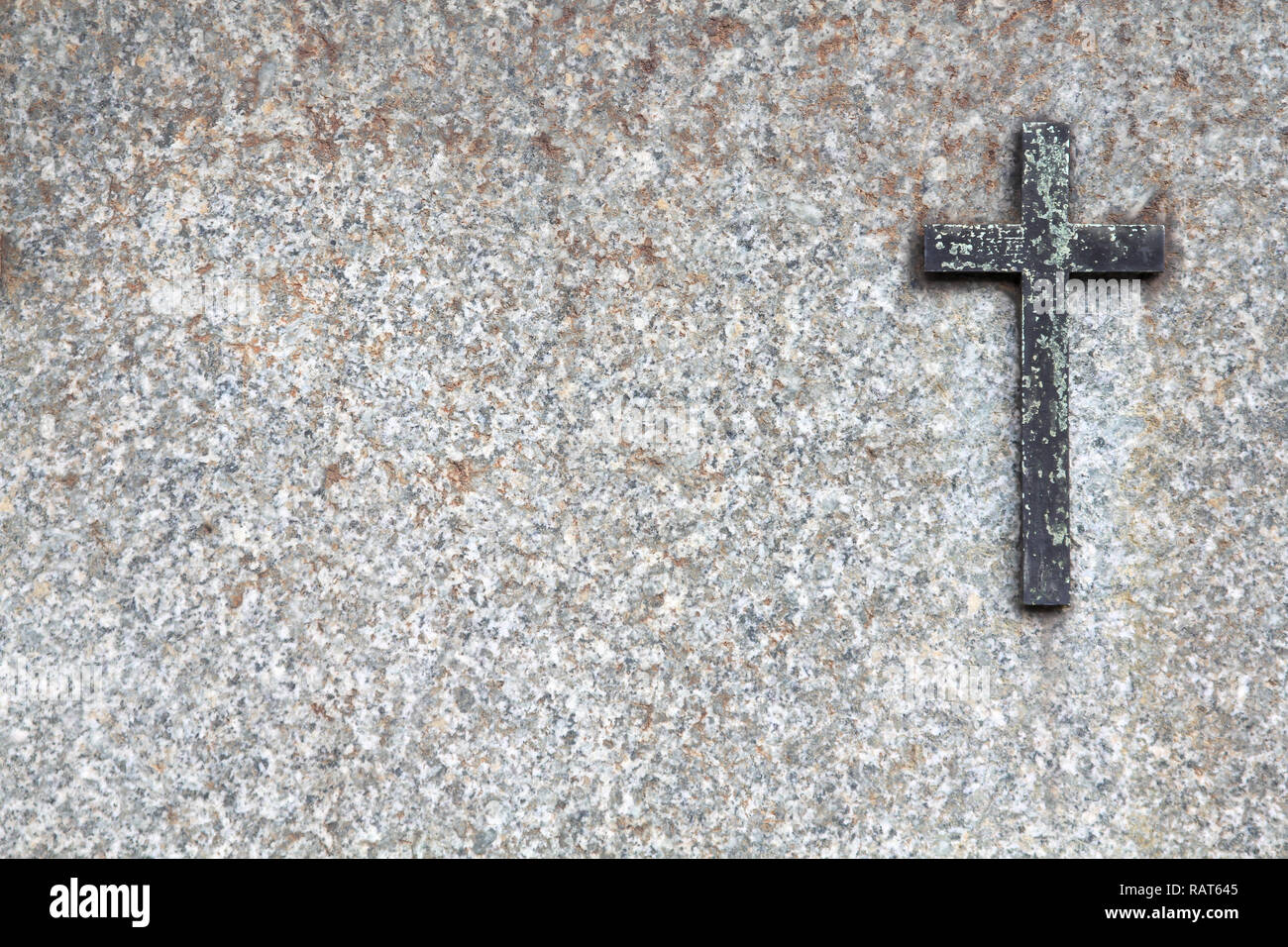 Gravestone texture - granite stone and a brass cross. Religious background. - Stock Image