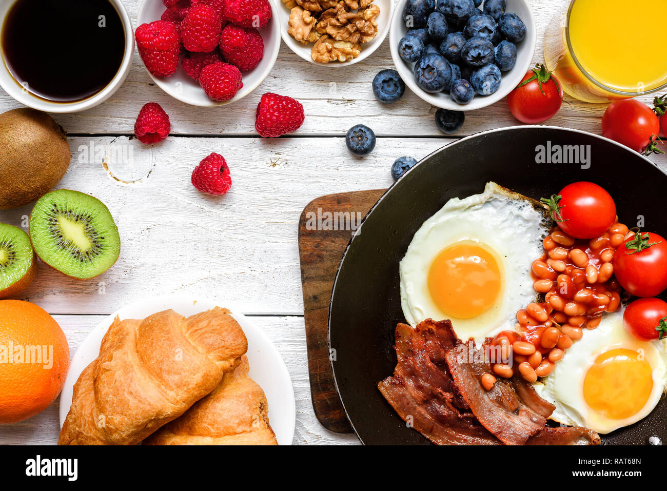 Breakfast including coffee, fried egg ,bacon, beans, croissant, orange juice with fruits and berries. top view - Stock Image