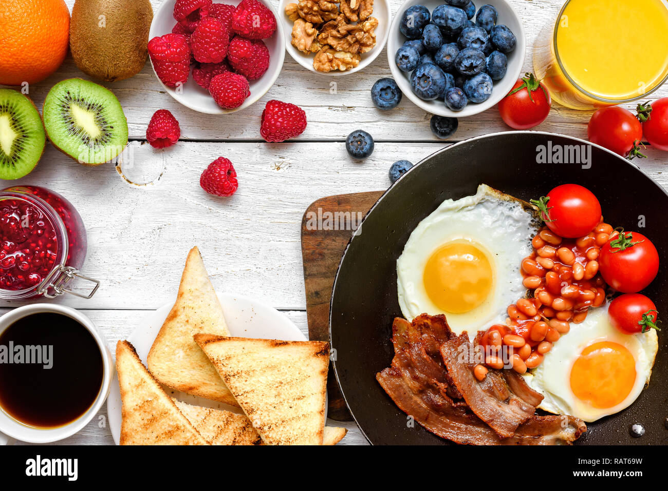 English breakfast - fried egg, beans, tomatoes, coffee, bacon and toast with fresh fruits and berries. Top view - Stock Image