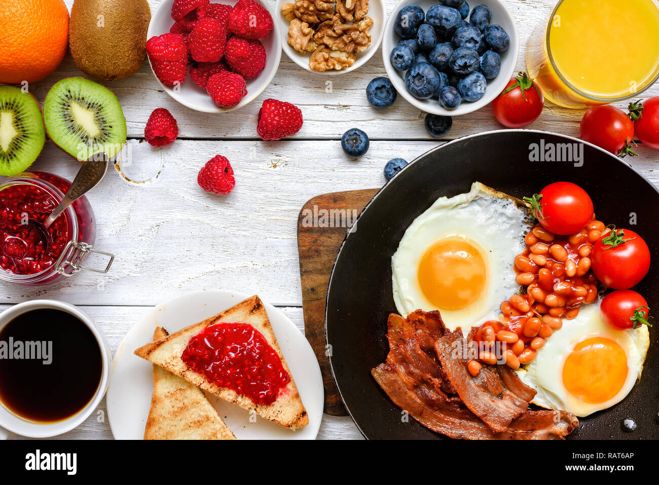 English breakfast - fried egg, beans, tomatoes, coffee, bacon and toast with orange juice, fresh fruits and berries. Top view - Stock Image