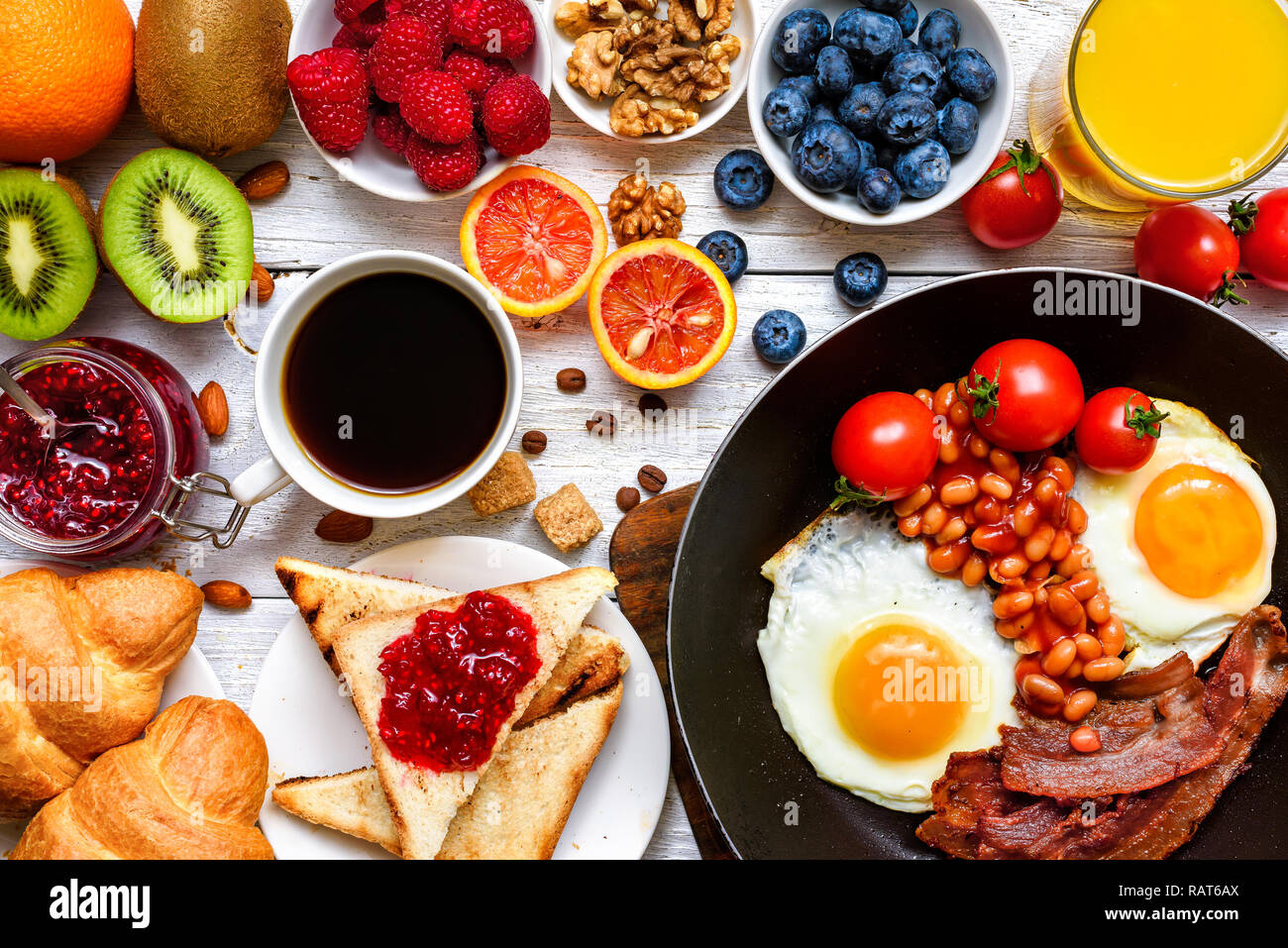 breakfast including coffee, fried egg, bacon, beans, toast, croissant, orange juice with fruits and berries. top view - Stock Image