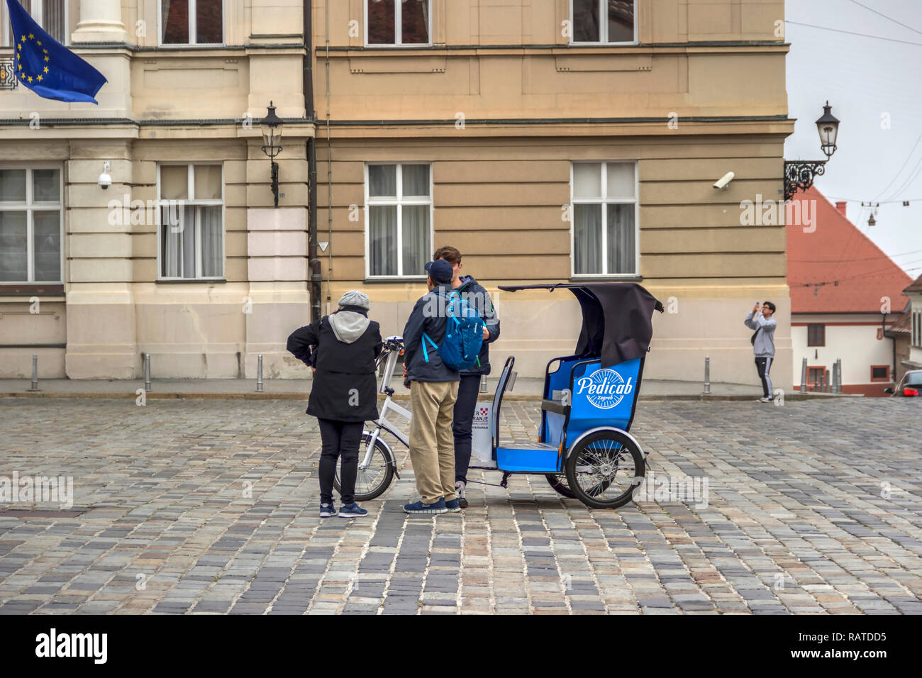 Zagreb, Croatia, November 2018 - Couple of tourists and driver standing next to an electric powered tricycle rickshaw 'Pedicab' at St. Mark's Square - Stock Image