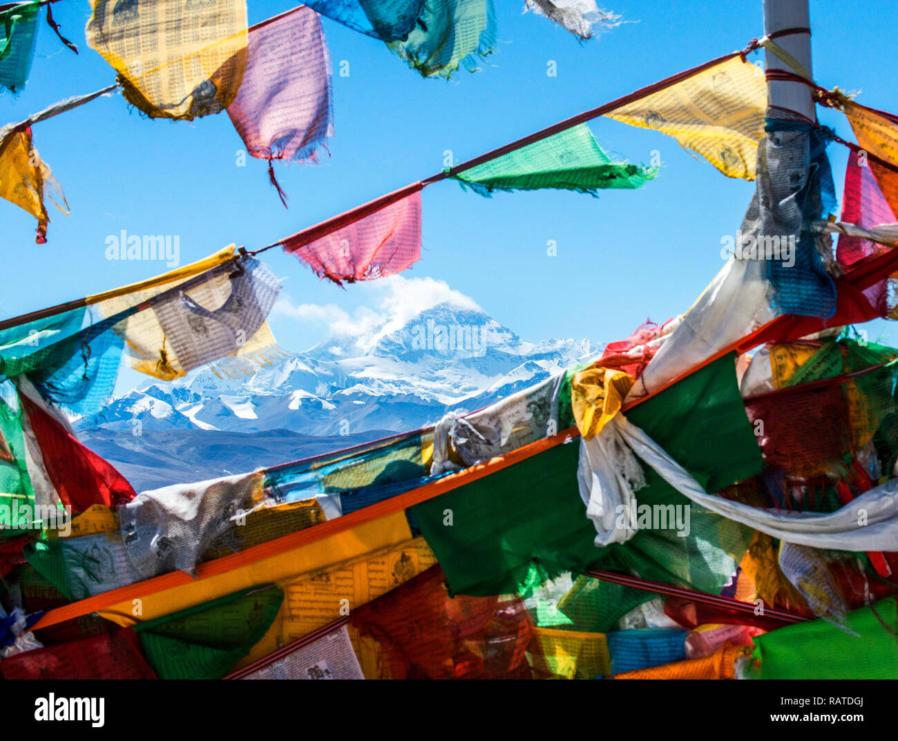 Mt Everest viewed through gap between prayer flags at pass on way to base camp - Stock Image