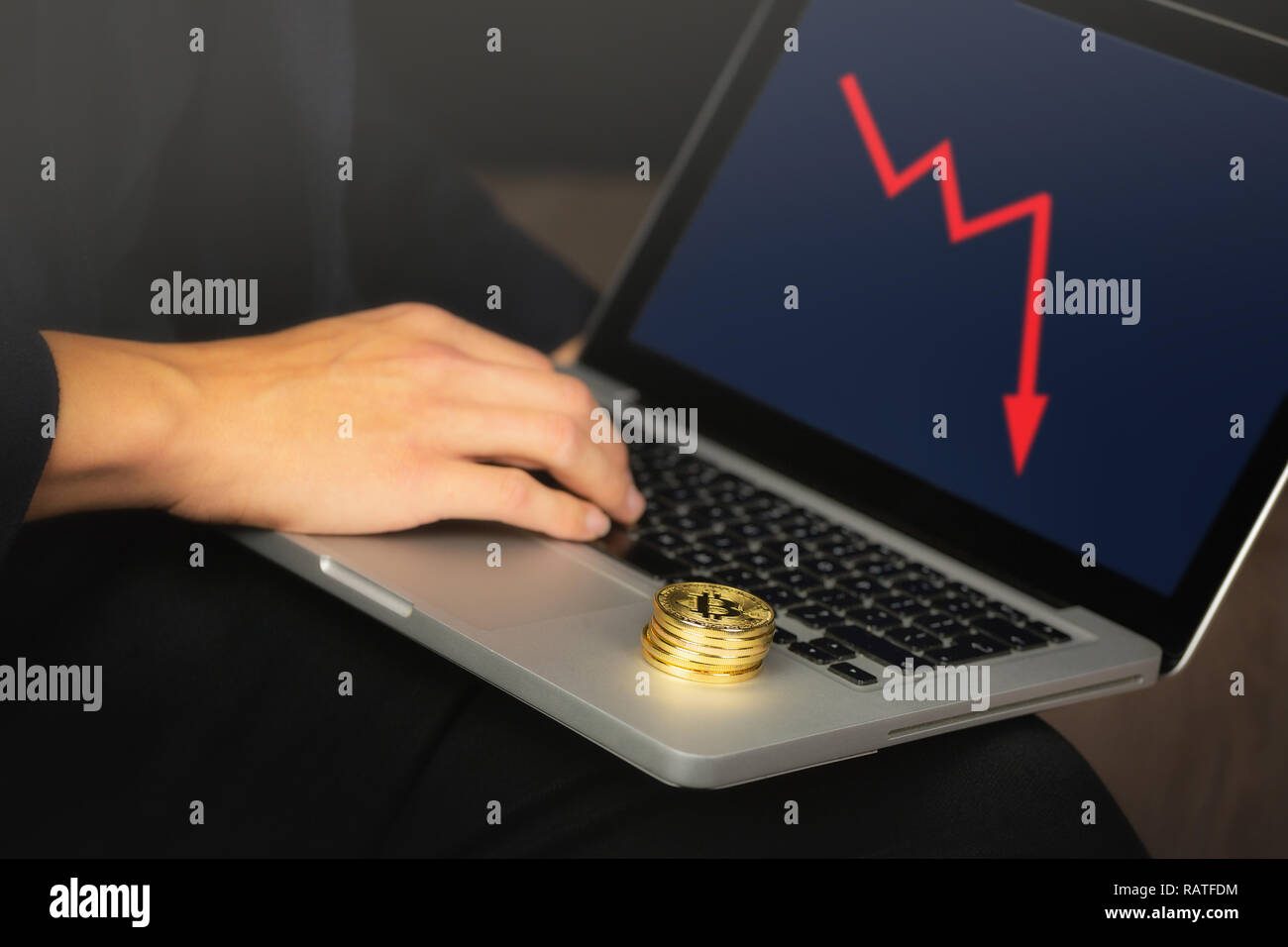 Businessman working on laptop with a golden bitcoin coins stack on it. Red chart, price crash concept. - Stock Image